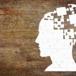 white puzzle of human head with missing pieces on a wooden background