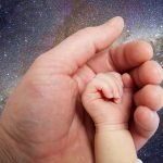 adult hand holding an infant's hand with Milky Way galaxy background