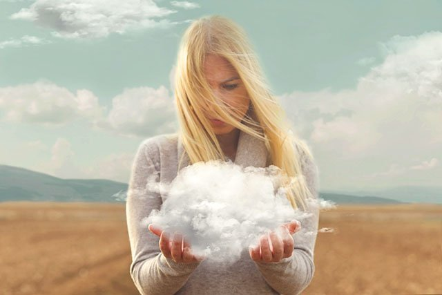 blond woman staring at a cloud in her hands