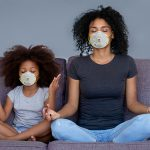 mother and young daughter meditating on a couch next to each other wearing P95 face masks for virus protection