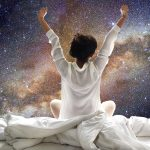 young woman dressed in white waking up from sleep in bed with her arms raised up in the air on a background of the Milky Way galaxy