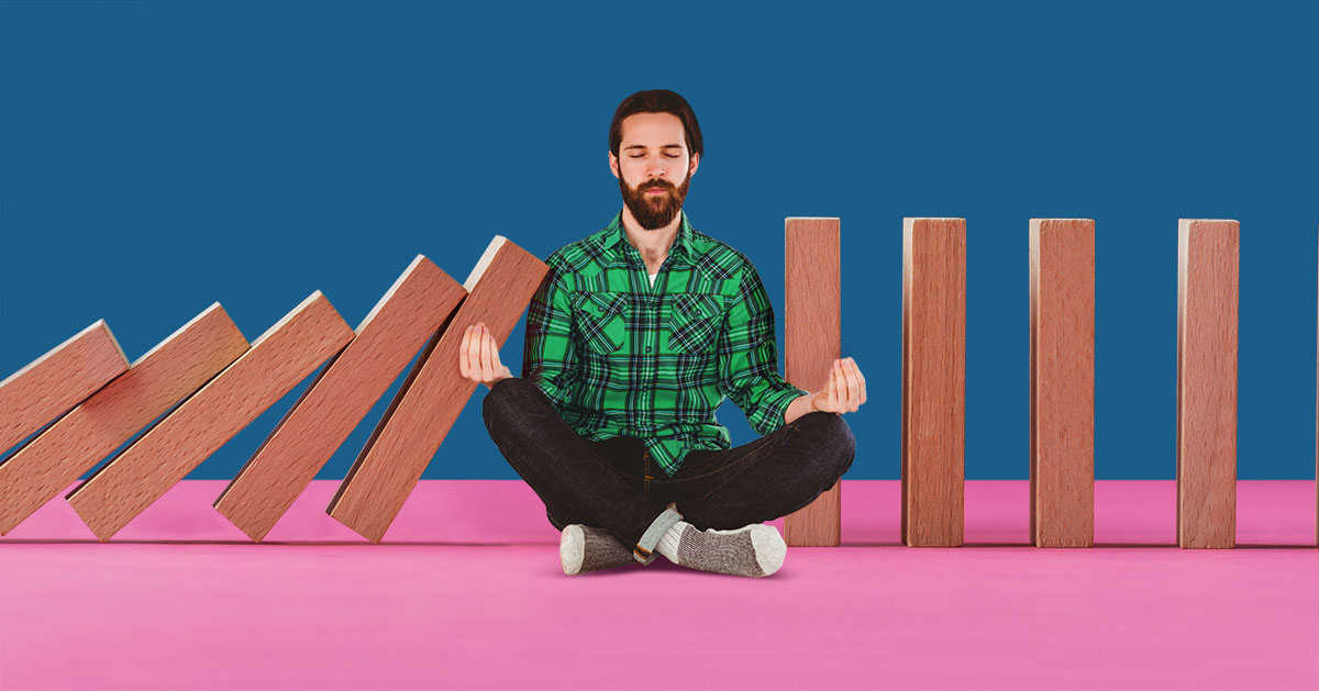 young bearded hipster man sitting in meditation position with legs crossed with wooden blocks fall against him in a domino-style