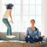 young brunette woman meditating with legs crossed on grey couch next to young girl happily jumping up and down on couch