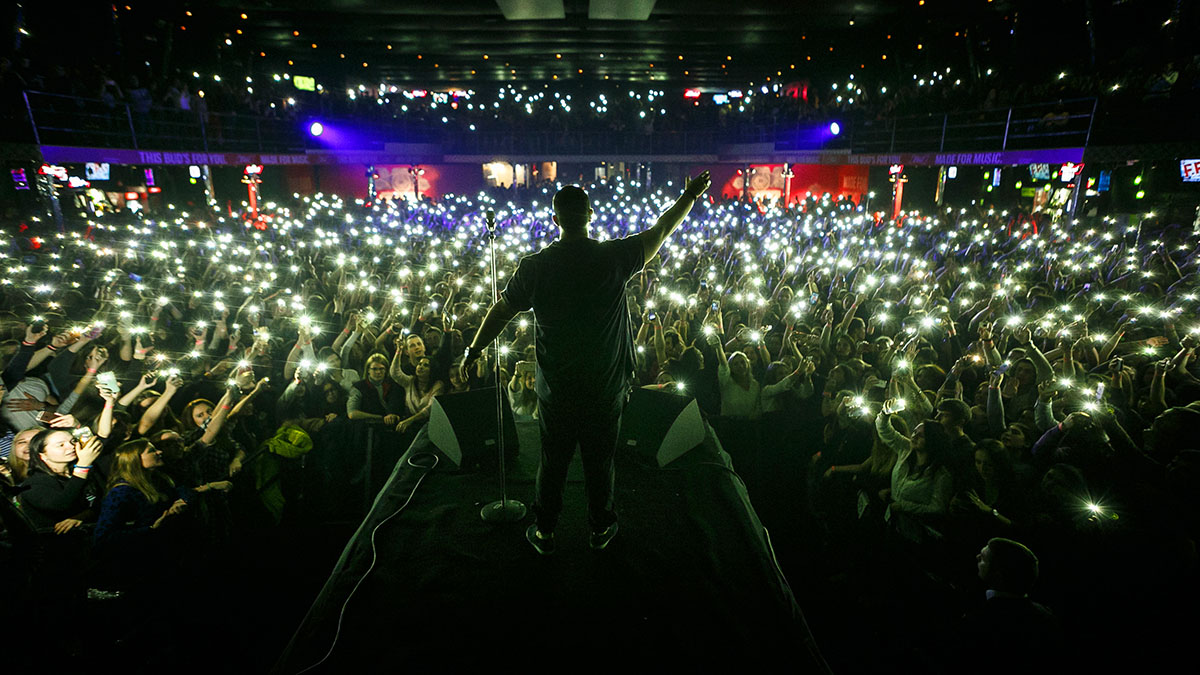 rapper on stage at concert facing crowd holding up phones