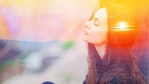 woman meditating with sunset double exposure in head