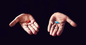 hands on dark background holding a red pill and a blue pill to choose