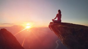 woman meditating on a mountain cliff watching the sunrise