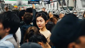 japanese woman on crowded subway car with eyes closed in meditation