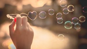 hand with bubble wand blowing heart shaped bubbles