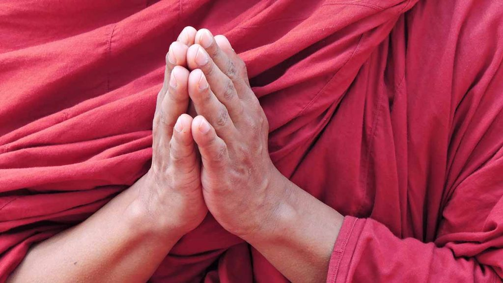Buddhist monk Dalai Lama hands in prayer for meditation and respect