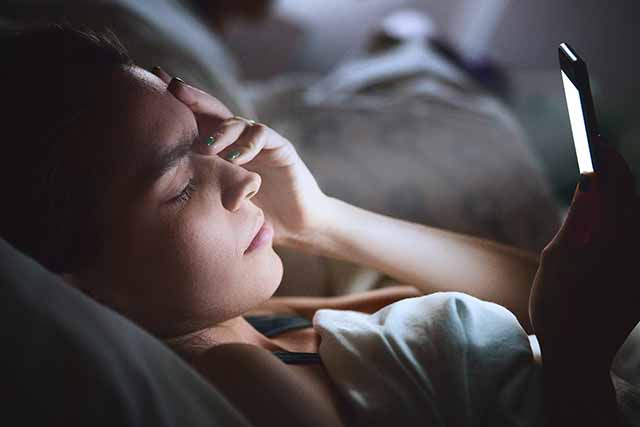 woman in bed with phone keeping her awake instead of a guided sleep meditation