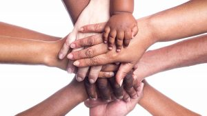 holding hands of many races, ages, and skin colors