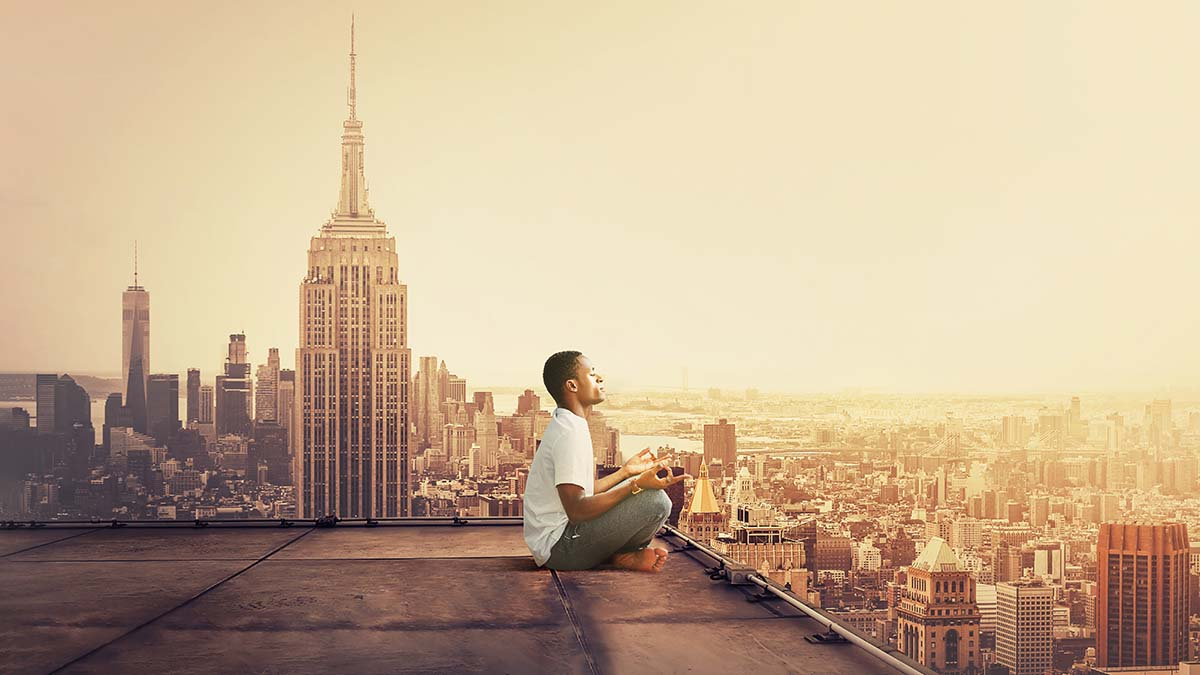 young adult Black African american man meditating on rooftop in New York City