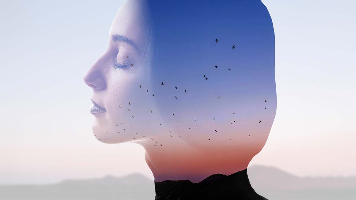peaceful photograph of woman in profile eyes closed, meditating, with double exposure of mountains and birds flying in the distance