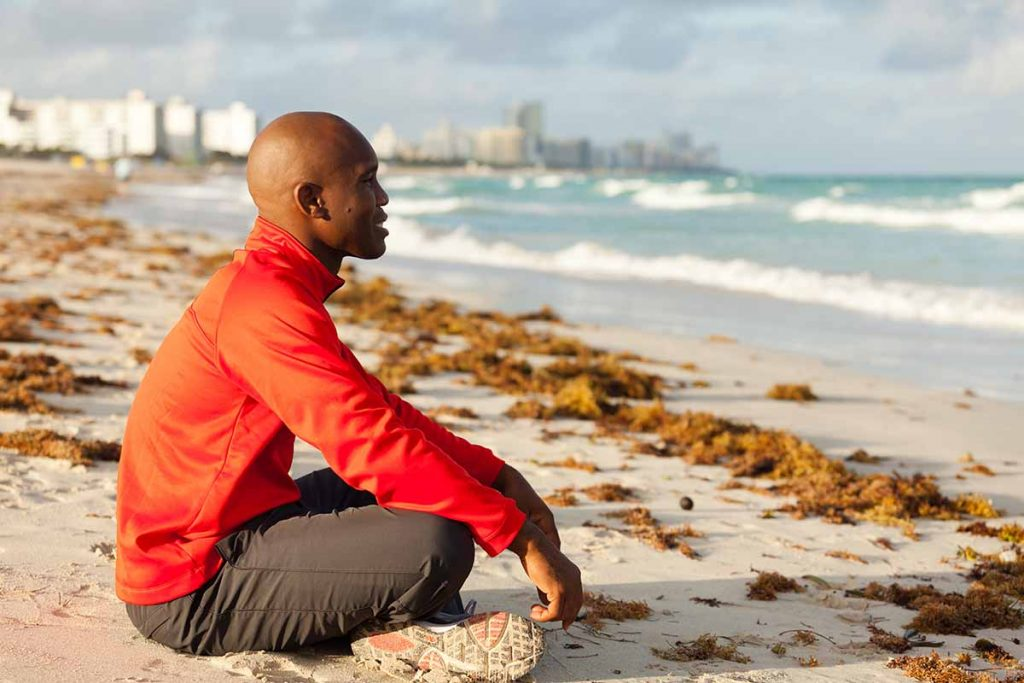 young adult black man meditating on the beach