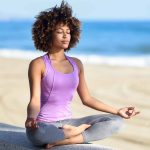 Young adult Black woman meditating on the beach