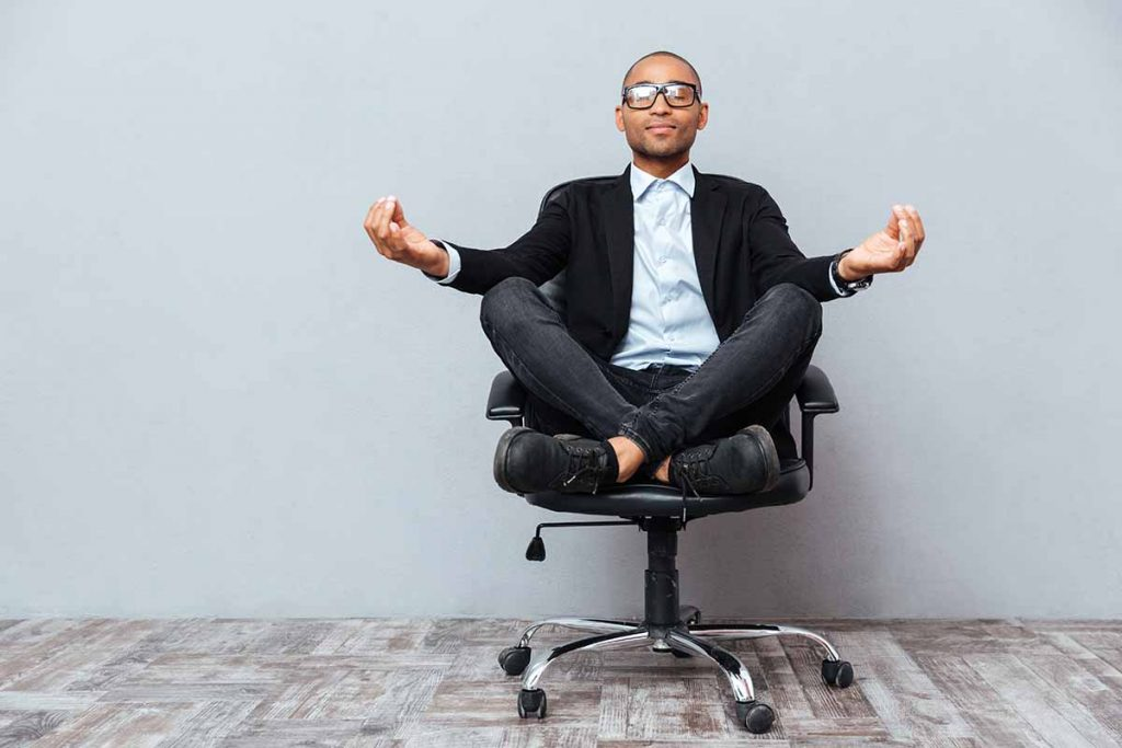 Young adult black man with glasses meditating in a rolling office chair
