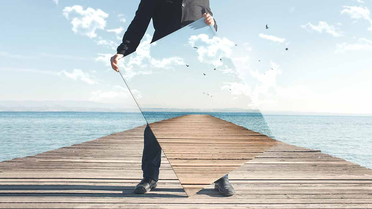 surreal image of a man standing on a pier holding a mirror that sees through him