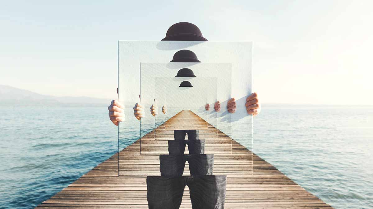 Surreal image of man on a pier with a mirror infinitely reflecting himself