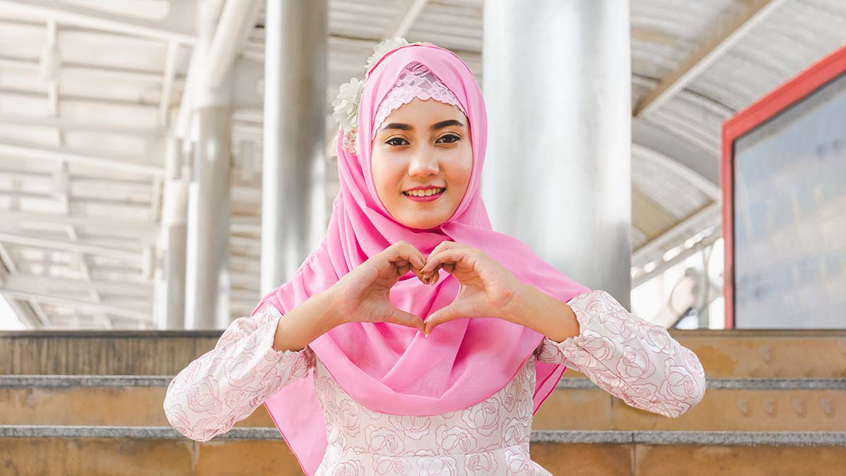 young happy islamic woman making heart with hands