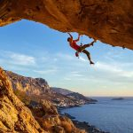 climber hanging from rock overhanging ocean