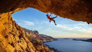 climber hanging from rock overhanging ocean