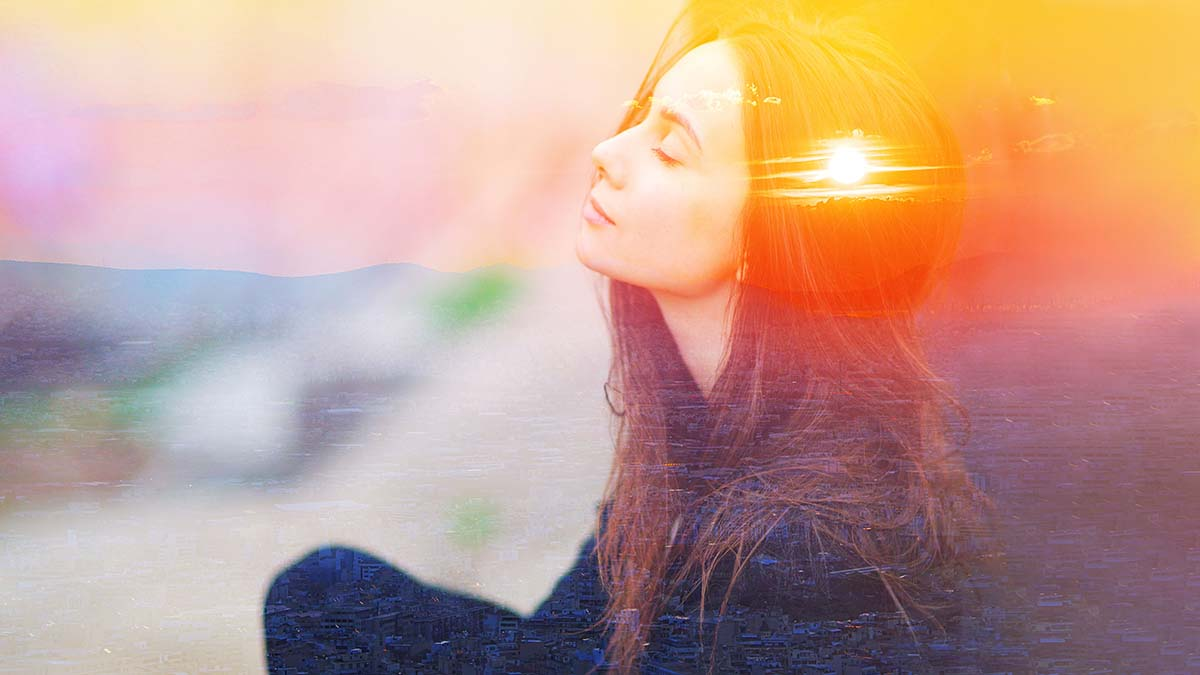 young woman leaning back meditating as the sun sets, double-exposed in her mind