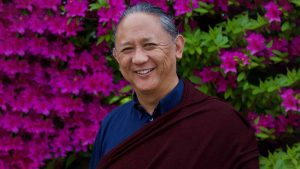 Dzigar Kongtrul Rinpoche lama, artist, Tibetan Buddhism in front of purple Flowers
