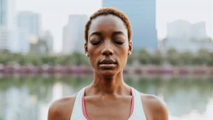 young Black woman meditating in the city by a lake