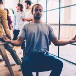 Young Black man meditating at work while people talk in the background