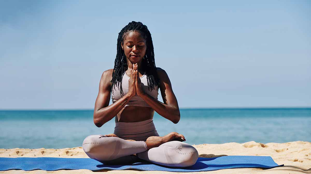 Young black woman meditating on the beach on a yoga mat