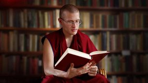 Ven. Gyalten Lekden in monk robes reading a Buddhist text