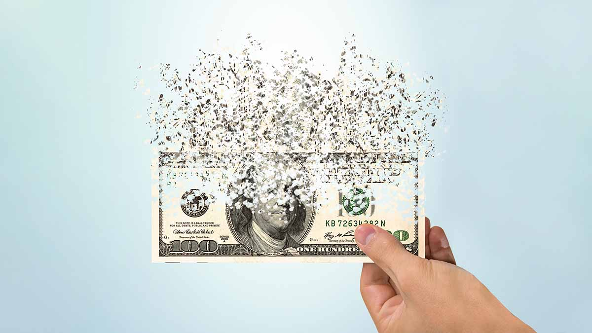 100 dollar bill dissolving into paticles held in a hand